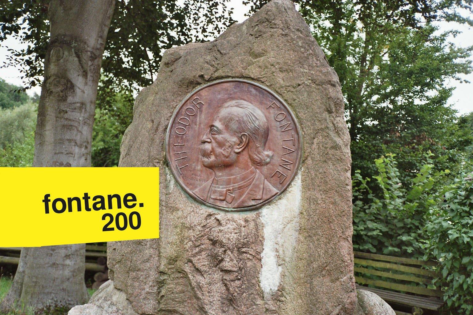 """Denkmal mit Theodor Fontane im Profil. Eine Treibarbeit, die in Falkenberg steht. Mit in das Bild montiert: das Logo des Fontanejahres: """"fontane. 200"""" in schwarzer Schrift auf gelben Grund."""