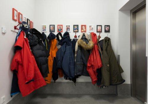Eine Garderobe: Jacken hängen an Haken. Darüber Bilder der Bewohnerinnen und Bewohner. Diese Bilder sind unkenntlich gemacht.