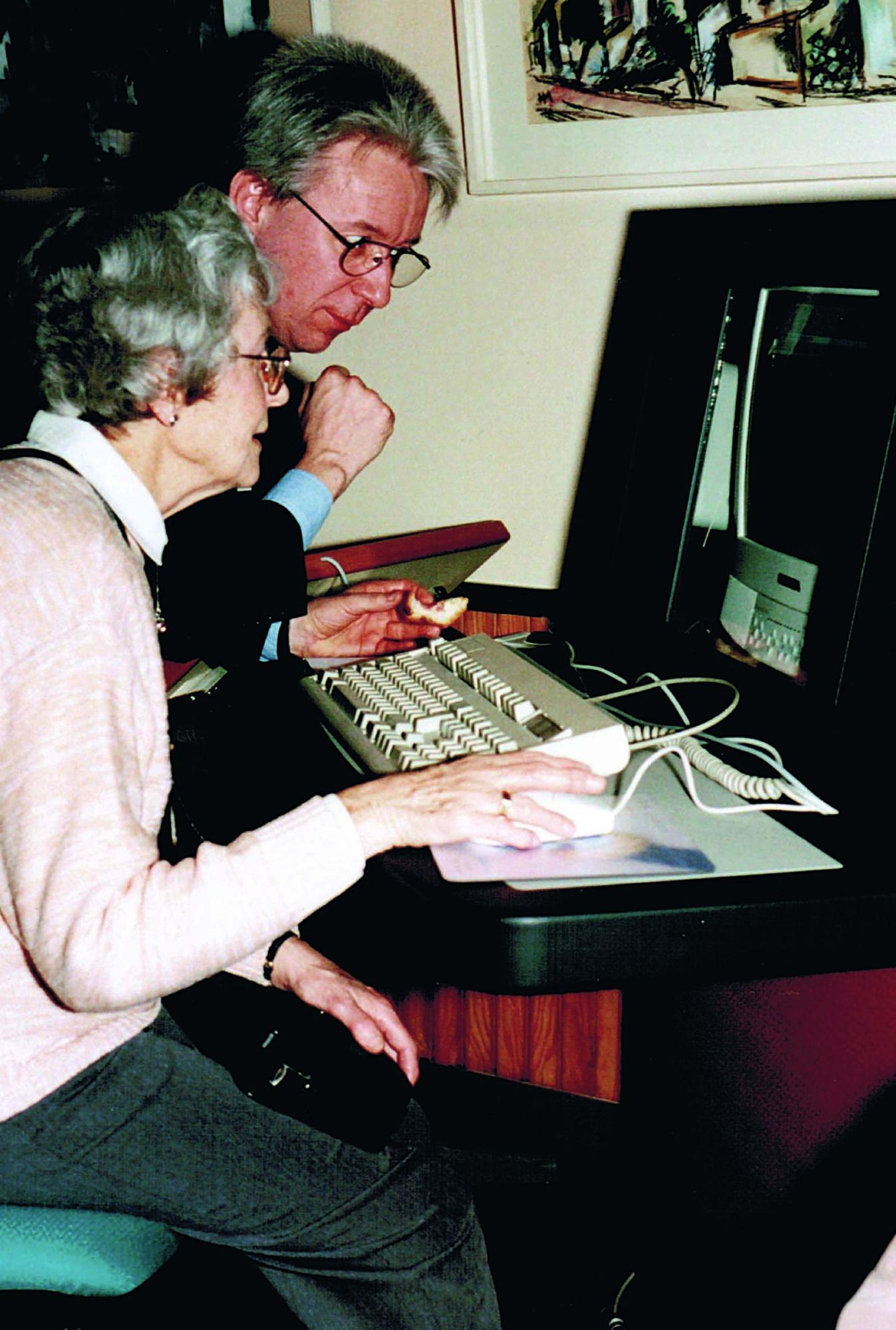 Zu sehen ist ein Mann, der sich über die Schulter einer älteren Dame lehnt. Die Dame schaut auf einen alten PC und hat die rechte Hand an der Maus.