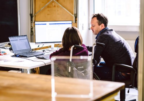 Eine Rollstuhlfahrerin und ein Mann sitzen gemeinsam vor einem Büroarbeitsplatz und sprechen miteinander.