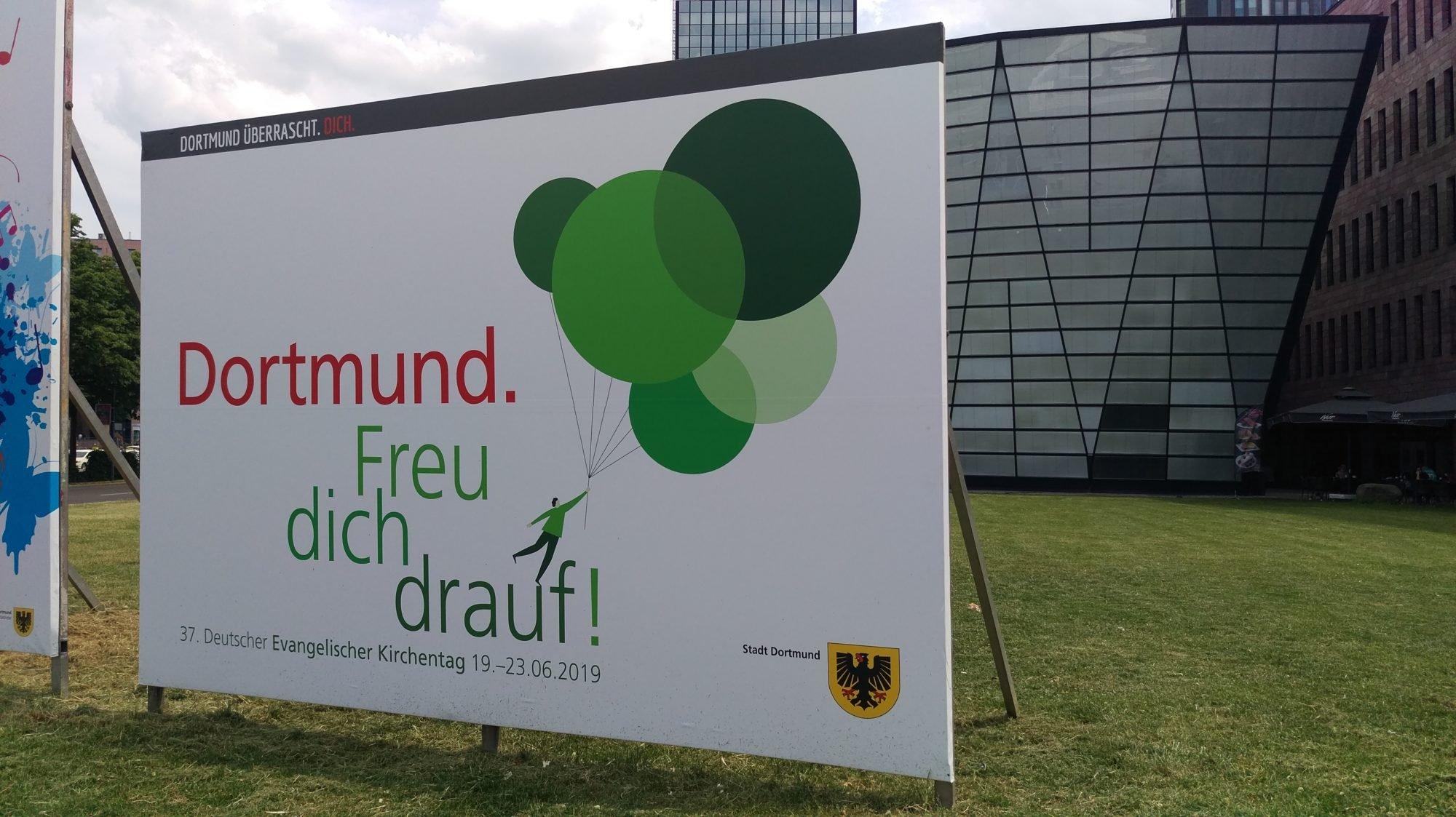 """Ein Werbeplakat für den 37. Deutschen Evangelischen Kirchentag mit der Aufschrift """"Dortmund. Freu dich drauf!"""" mit einer gezeichneten Figur, die an Luftballons hängt und davonfliegt sowie einem Wappen der Stadt Dortmund im unteren rechten Eck."""