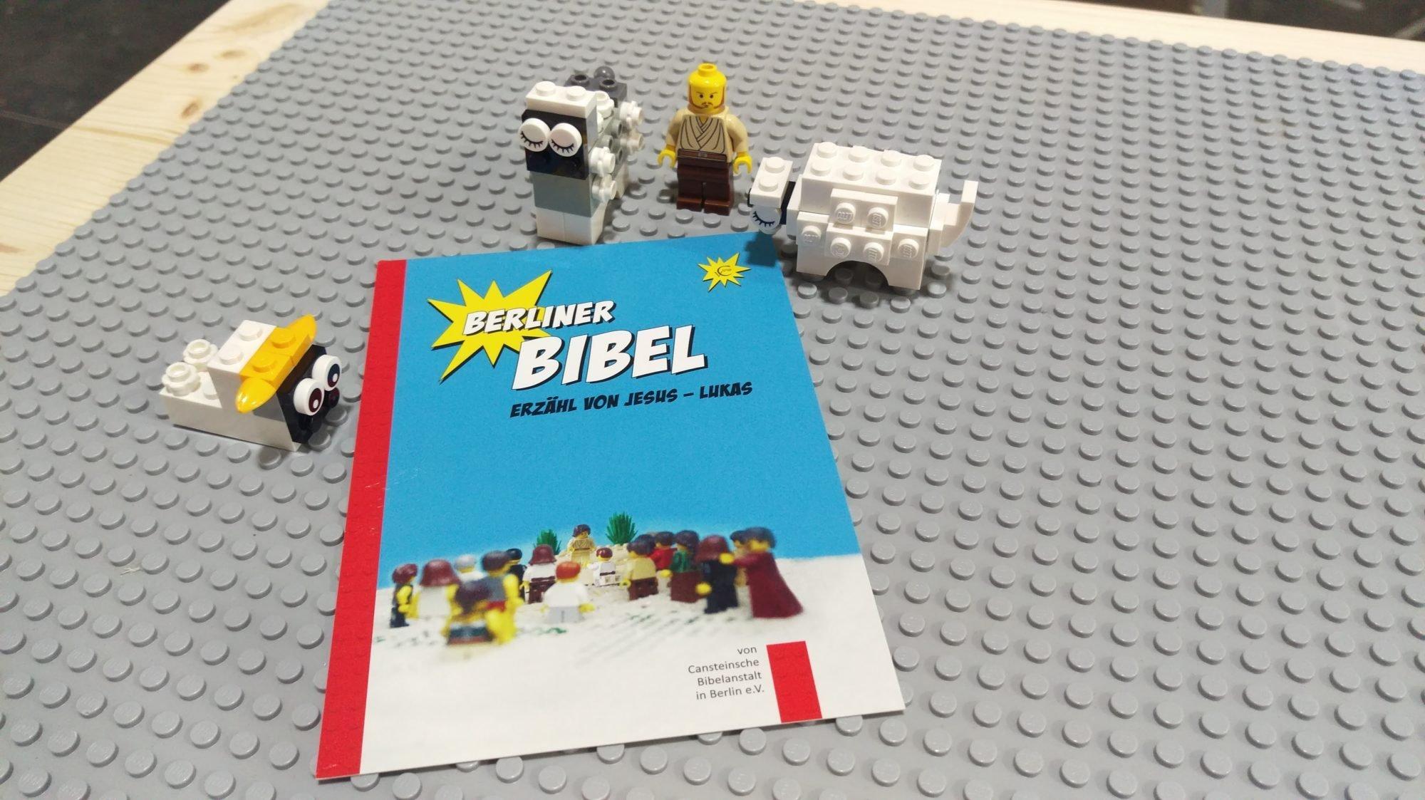 """Eine Lego-Miniatur und drei Schafe aus Legosteinen auf einem grauen Lego-Untergrund. Darauf liegt ein Flyer mit der Aufschrift: """"Berliner Bibel. Erzähl von Jesus - Lukas"""""""
