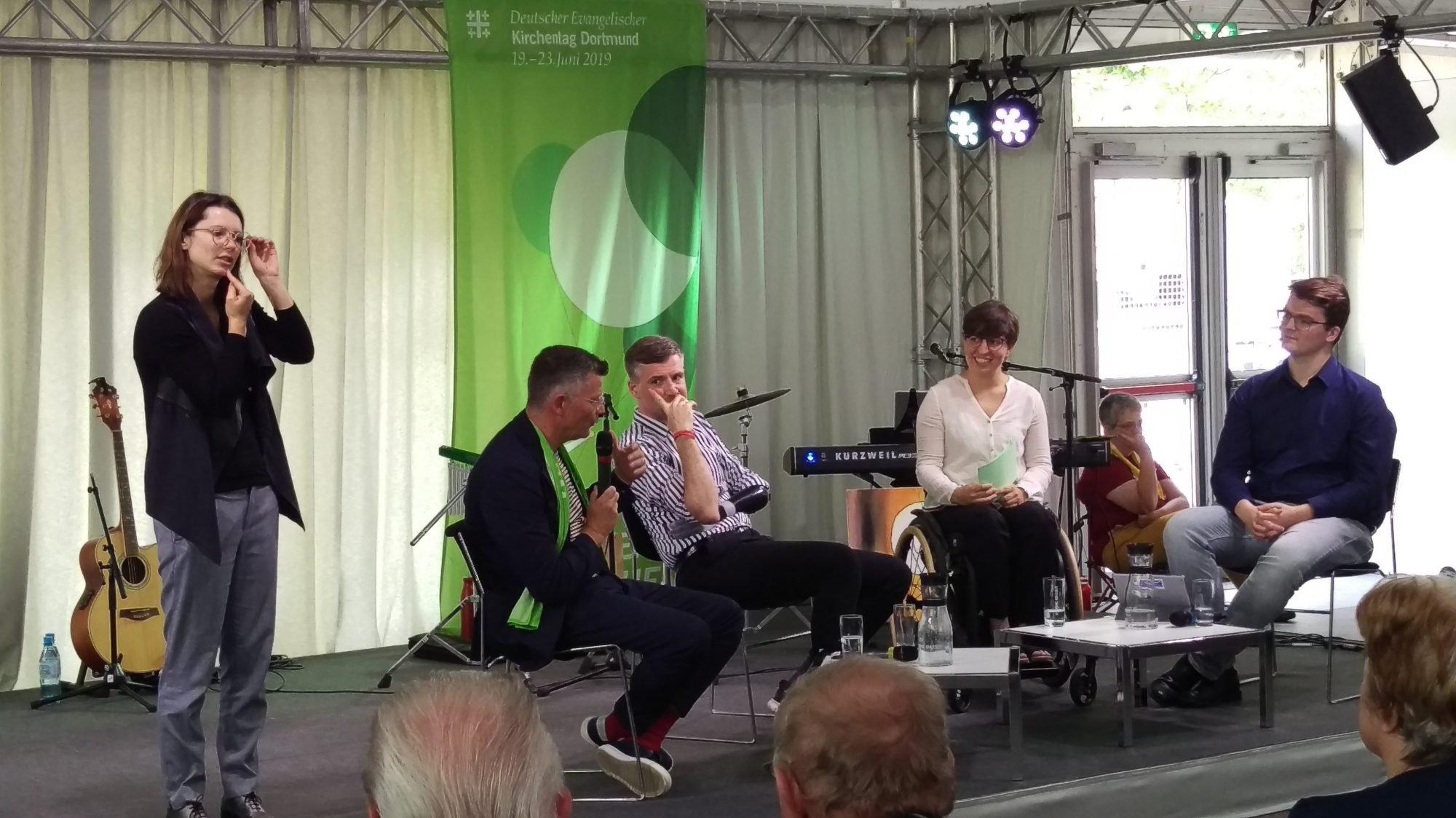 Ein Gruppe sitzt auf dem Podium und diskutiert. Links ein älterer Herr, neben ihm ein junger Mann, daneben eine junge Frau im Rollstugl und ganz rechts ein junger Mann mit Brille. Links im Bild ist eine Gebärdensprach-Dolmetscherin zu sehen.