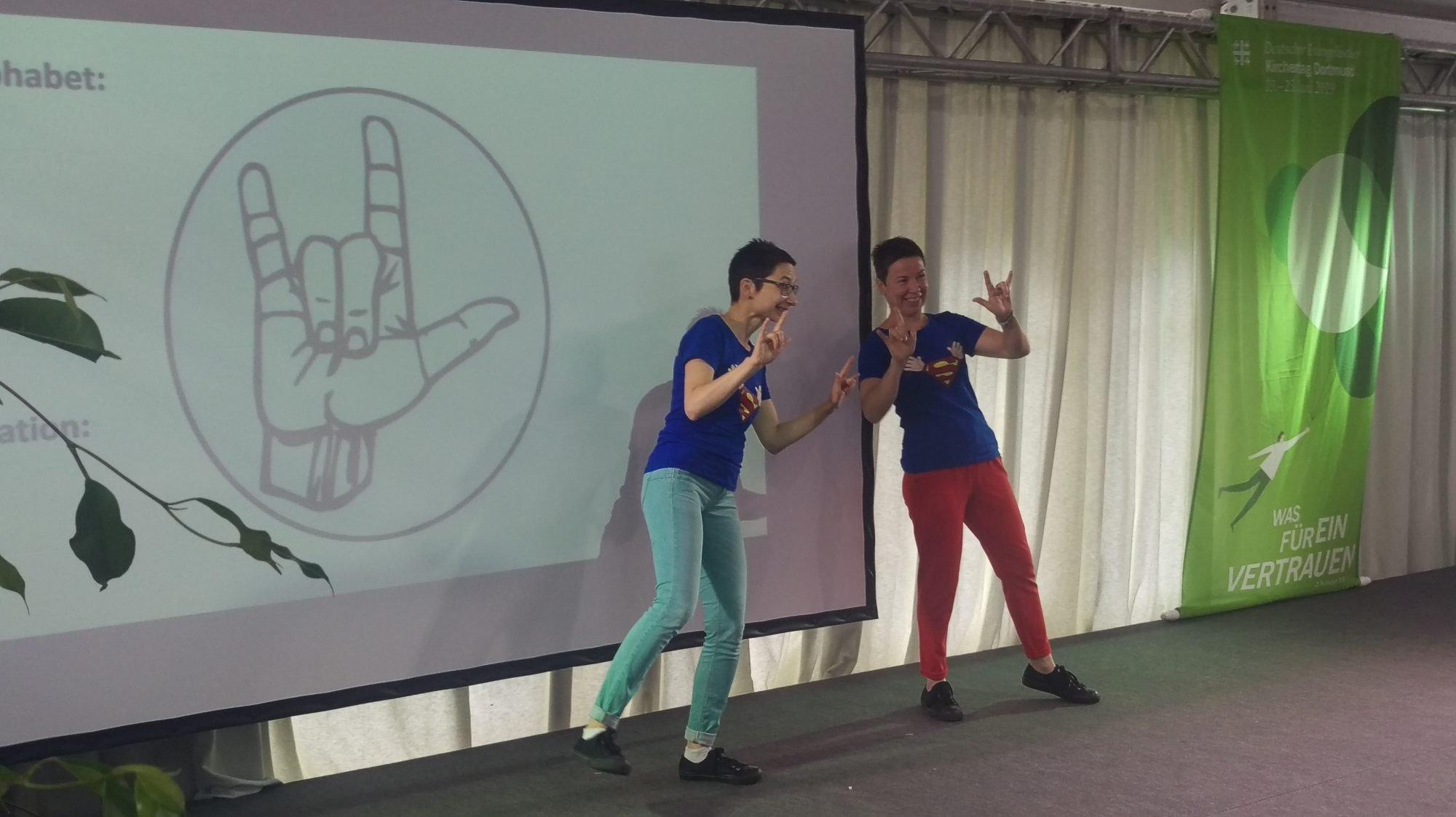 Zwei Dolmetscherinnen für die Deutsche Gebärdensprache auf der Bühne zeigen das Gebärden-Alphabet.
