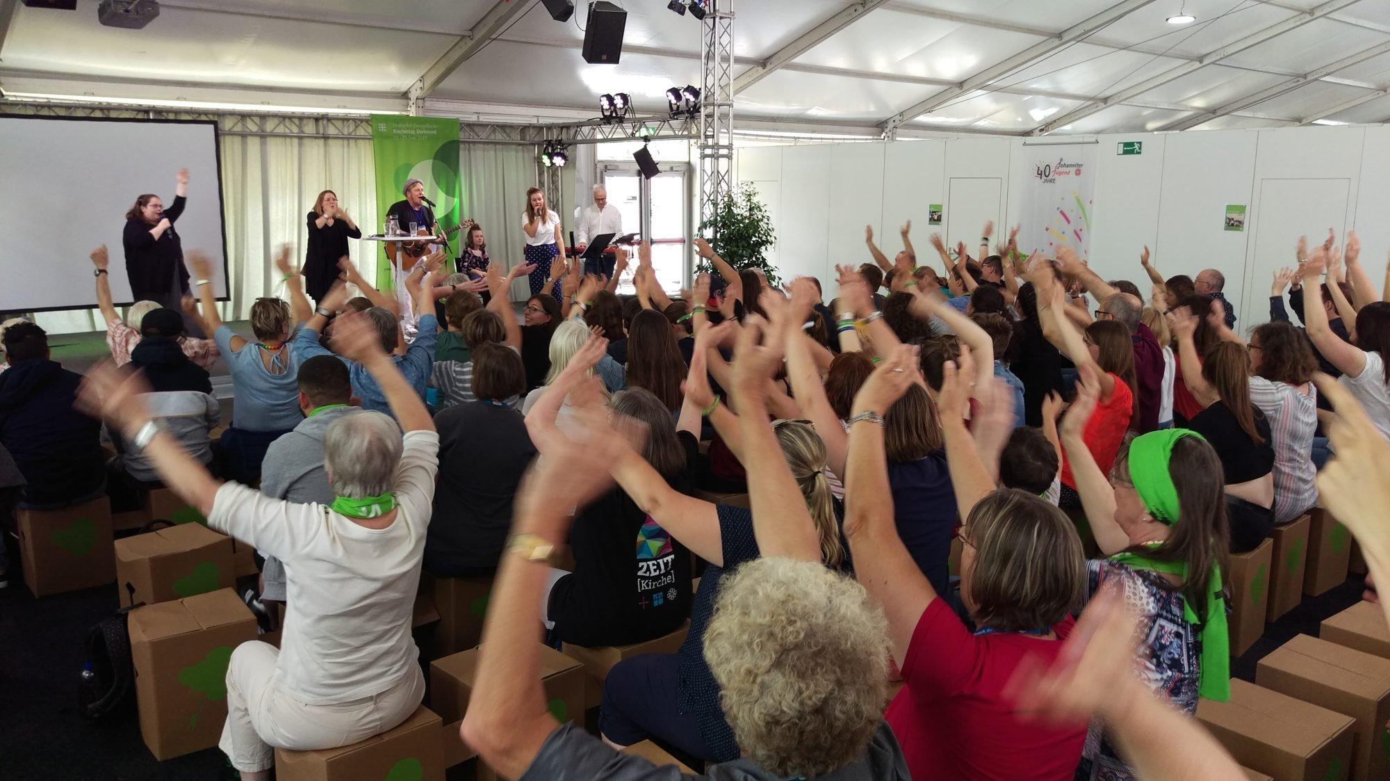Foto über die Köpfe des Publikums hinweg. Alle Hände gehen nach oben. Auf der Bühne spielt die Band.