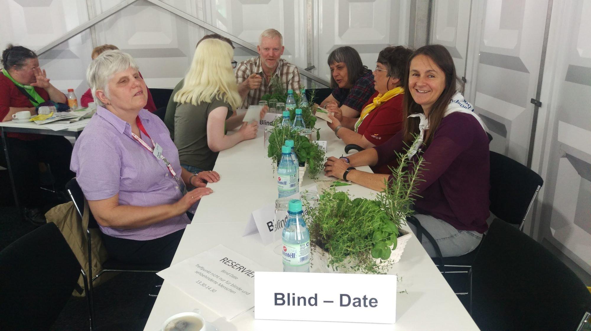 """Mehrere Personen, mit und ohne Sehbehinderungen, sitzen sich an einem Tisch gegenüber und sind in Gespräche vertieft. Alle lächeln oder sehen gut gelaunt aus. Auf dem Tisch stehen grüne Pflanzen, Wasserflaschen und Schilder mit der Aufschrift: """"Blind Date"""""""