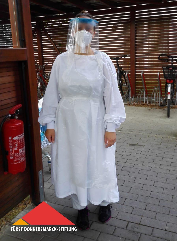 Yvonne Grabow trägt einen Schutzkittel, eine Mund-Nasen-Maske und ein Schutzvisier.