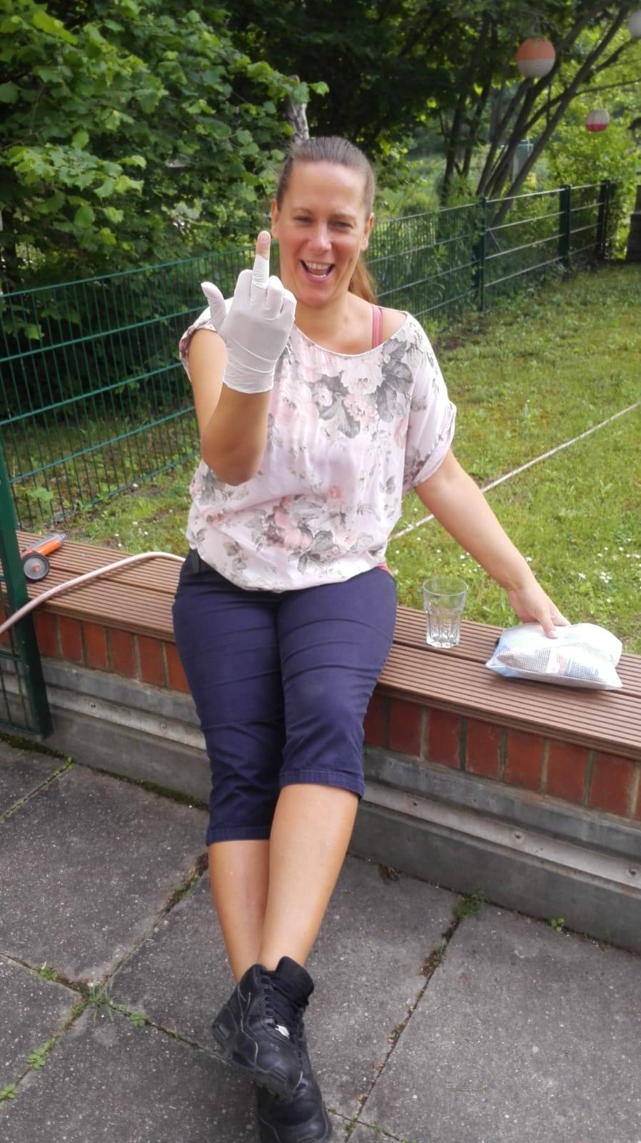 Yvonne Grabow lacht in die Kamera. Sie hat einen Gummihandschuh an, der am Mittelfinger gerissen ist. Sie streckt den Mittelfinger aus.