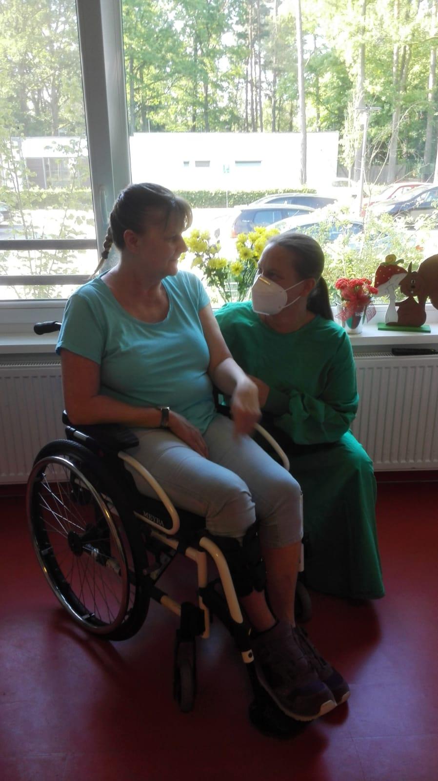 Eine Pflegerin in Schutzkleidung kniet neben einer Klientin im Rollstuhl. Sie trägt Mundschutz und ist der Klientin direkt zugewandt.