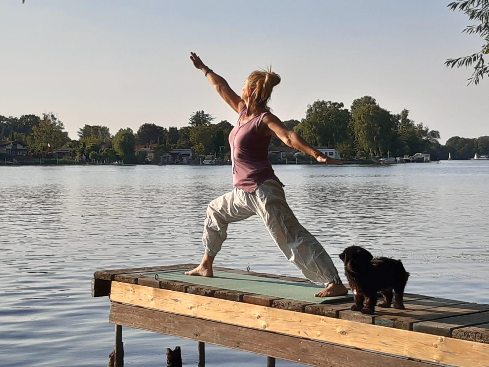 Daniela von Langen macht auf einem Steg eine Yogaübung. Neben ihr steht ein kleiner schwarzer Hund.