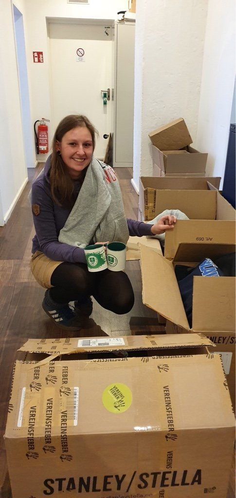 Eine Helferin mit Kartons voller Sachspenden.