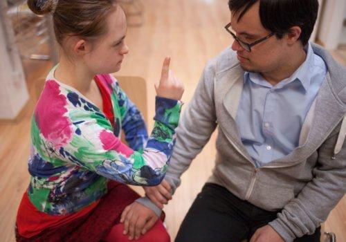 """Eine junge Frau und ein junger Man mit Down-Syndrom: Er fasst sie ans Bein und sie zeigt mit dem Finger, um ein """"Nein"""" zum Ausdruck zu bringen."""