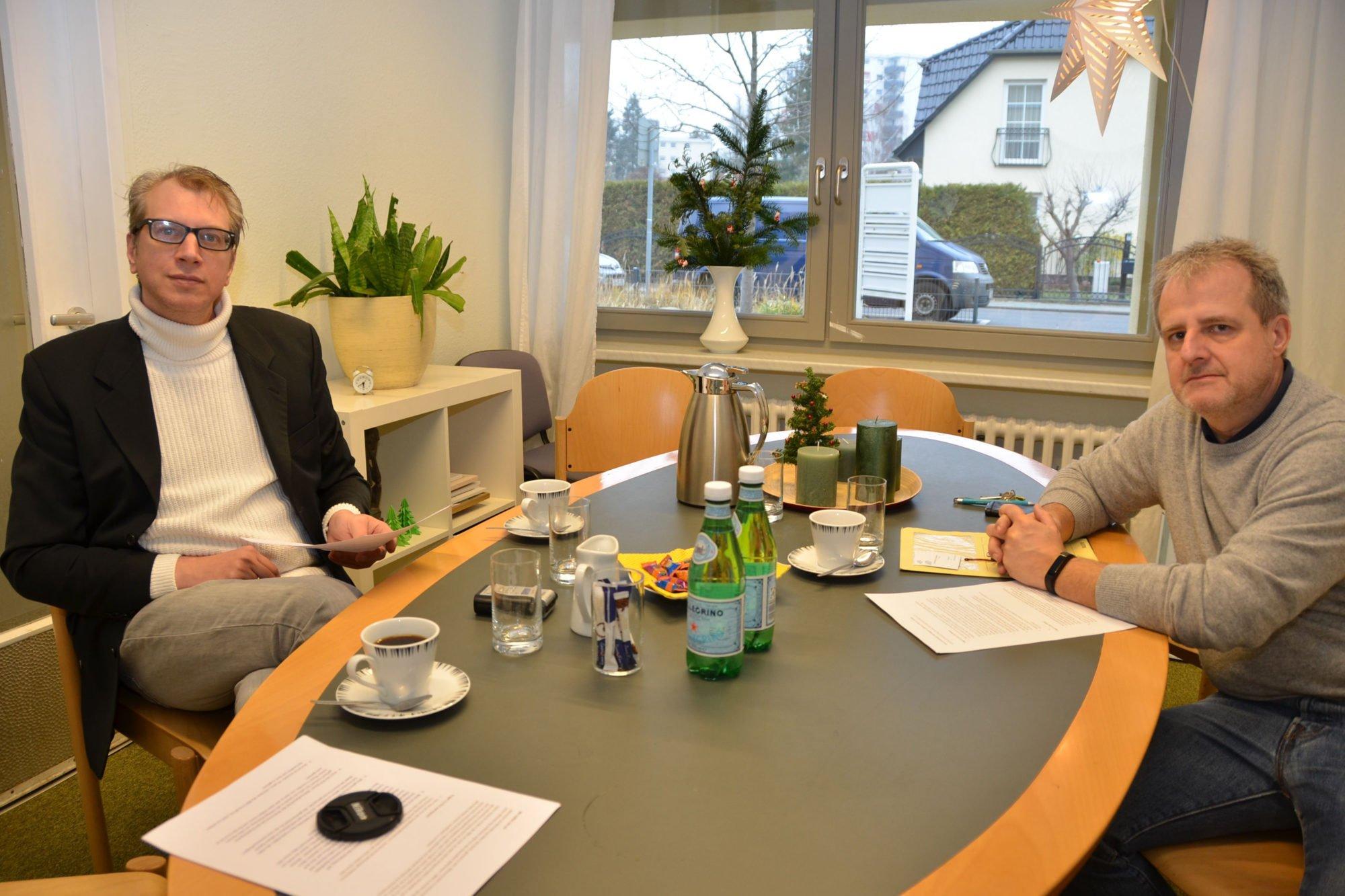 Redakteur Martin Küster sitzt an einem großen ovalen Meeting-Tisch, ihm gegenüber Michael Ertel. Beide schauen Richtung Kamera. Auf dem Tisch stehen Wasserflaschen, Gläser und Kaffeetassen.