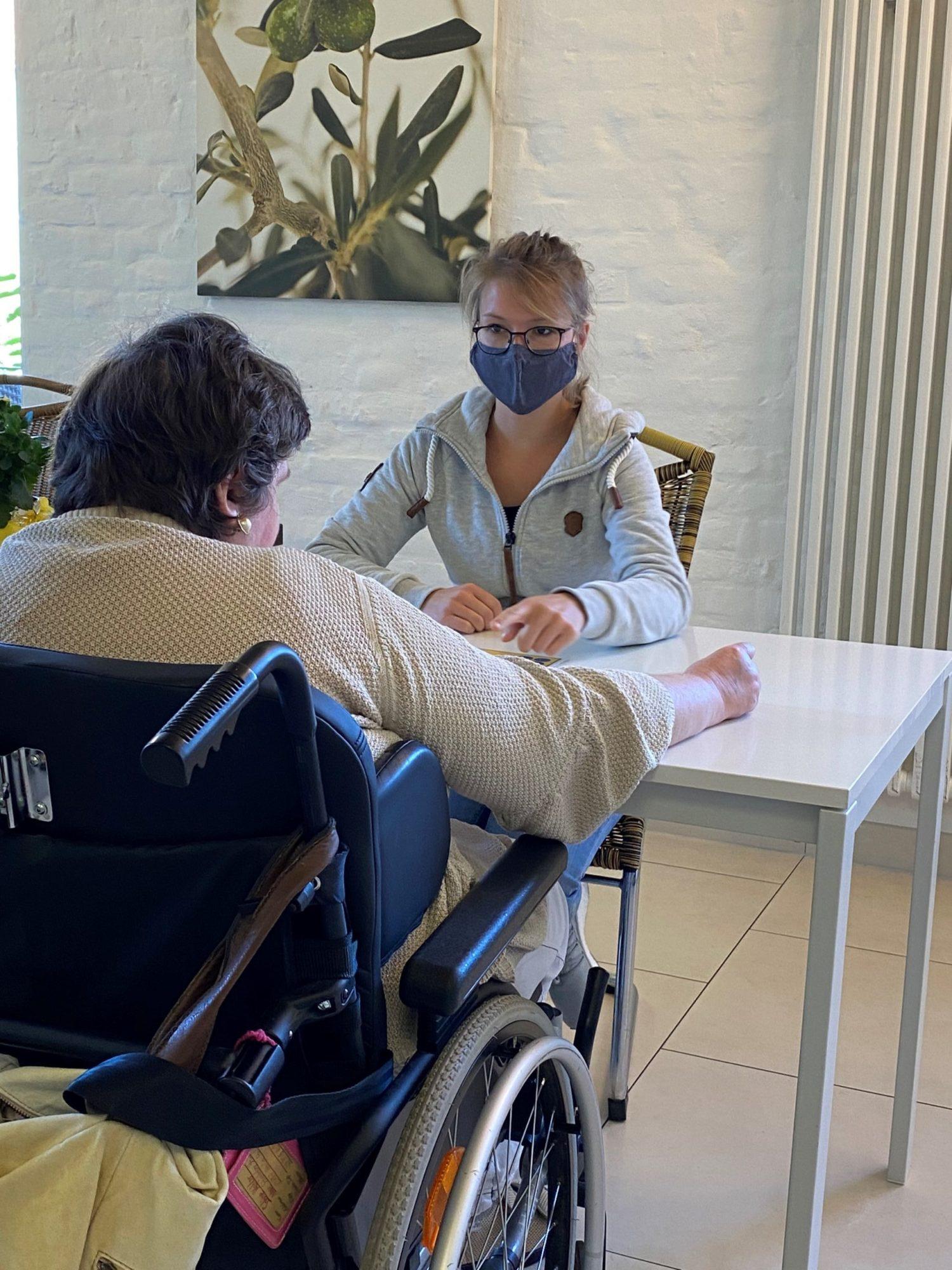 Anna Kühnert sitzt mit einer Klientin im Rollstuhl gemeinam an einem Tisch.