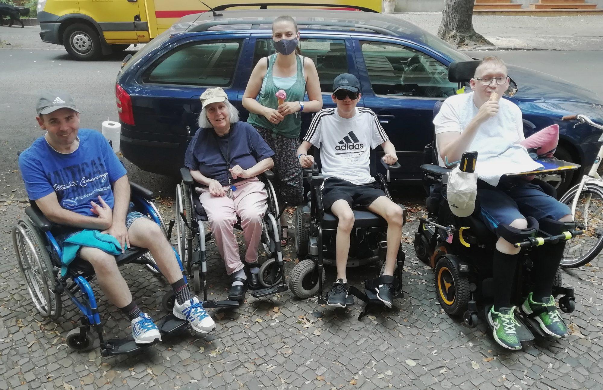 Larissa Bögel unterwegs mit drei Klienten und einer Klientin, die alle im Rollstuhl unterwegs sind.