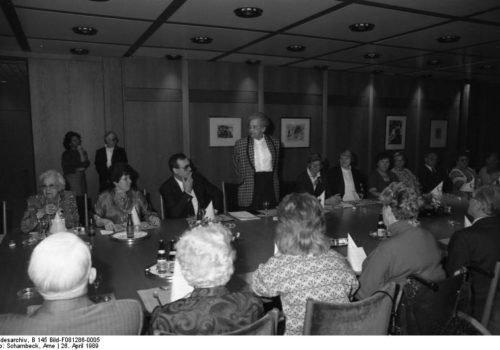 Ein historisches Schwarz-Weiß-Bild: Lieselotte Berger stehend an einem Tisch mit vielen anderen behinderten und nicht-behinderten Personen.