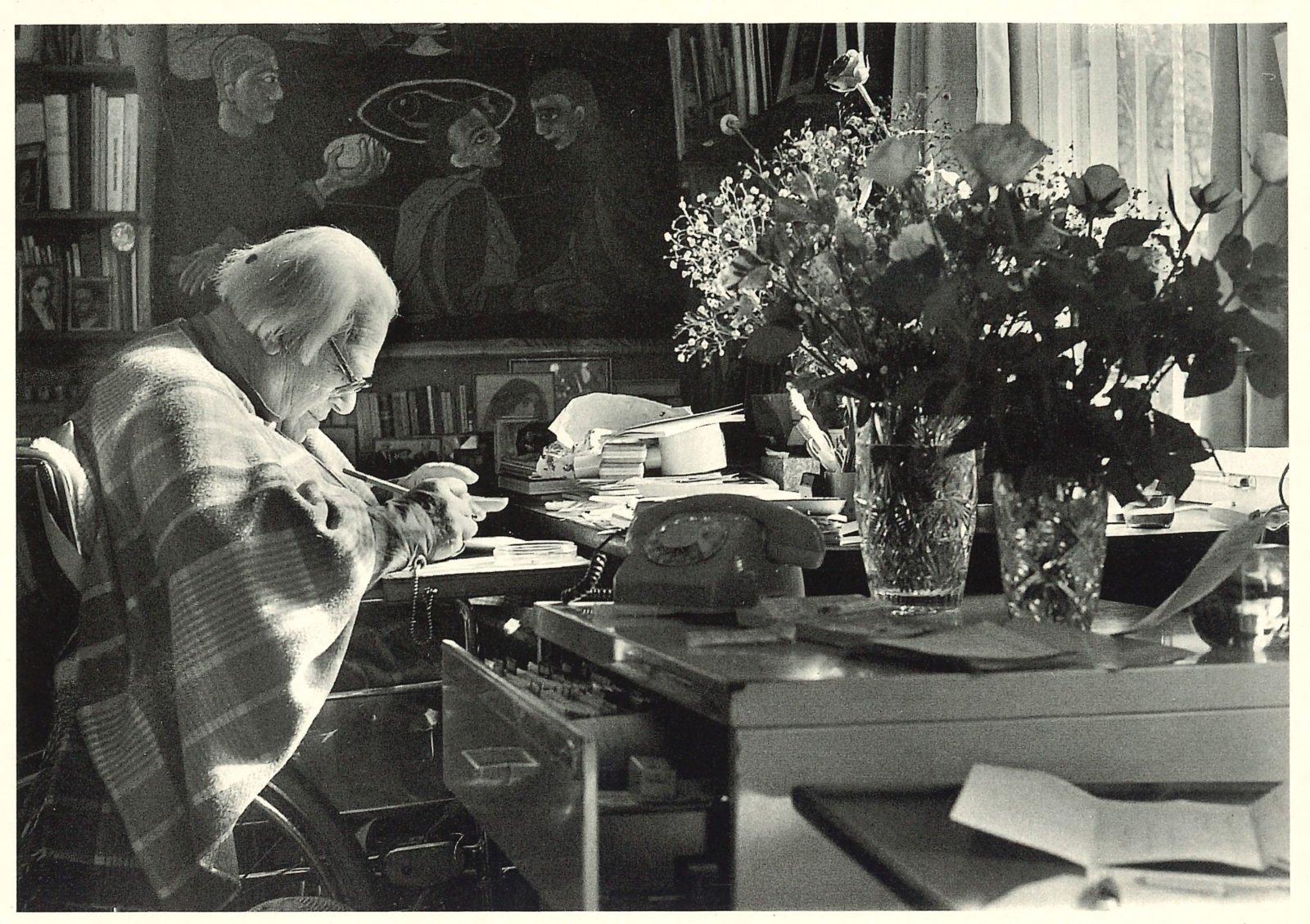 Eine Postkarte, die Lindenberg im Rollstuhl sitzen an seinem Schreibtisch zeigt. Auf demTisch stehen Blumen, ein Telefon mit Wählscheibe und diverse Dokumente und Bücher.