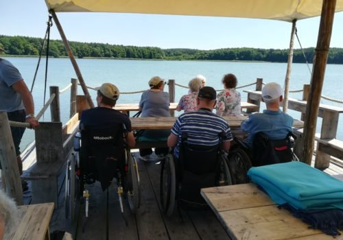 Eine Gruppe von sieben Menschen, davon drei im Rollstuhl sitzen auf einem hölzernen Floß und blicken au den See. Sie sind von hinten fotografiert, man sieht deshalb ihre Rücken. Das Wetter ist gut, das Wasser blau.