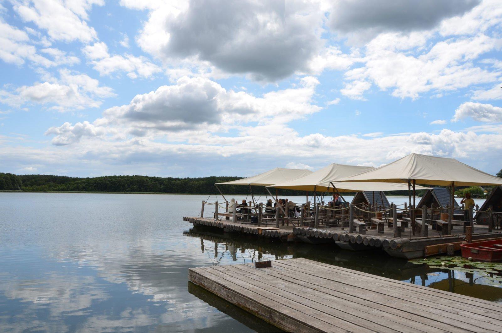 Vorne rechts ein hölzerner Steg. Dahintrer drei aneinandergebundene Flöße aus Holz mit Zeltdächern. Im Hintergrund grüner Wald, oben blauer Himmel mit vielen großen Wolken, die sich im Wasser des Sees spiegeln.