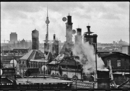 Schwarz-Weiß-Foto über den Dächern Berlins: Die Schornsteine der alten Mälzerei in Pankow sind zentral im Bild zu sehen, drumherum weitere Dächer und im Hintergrund der Fernsehturm