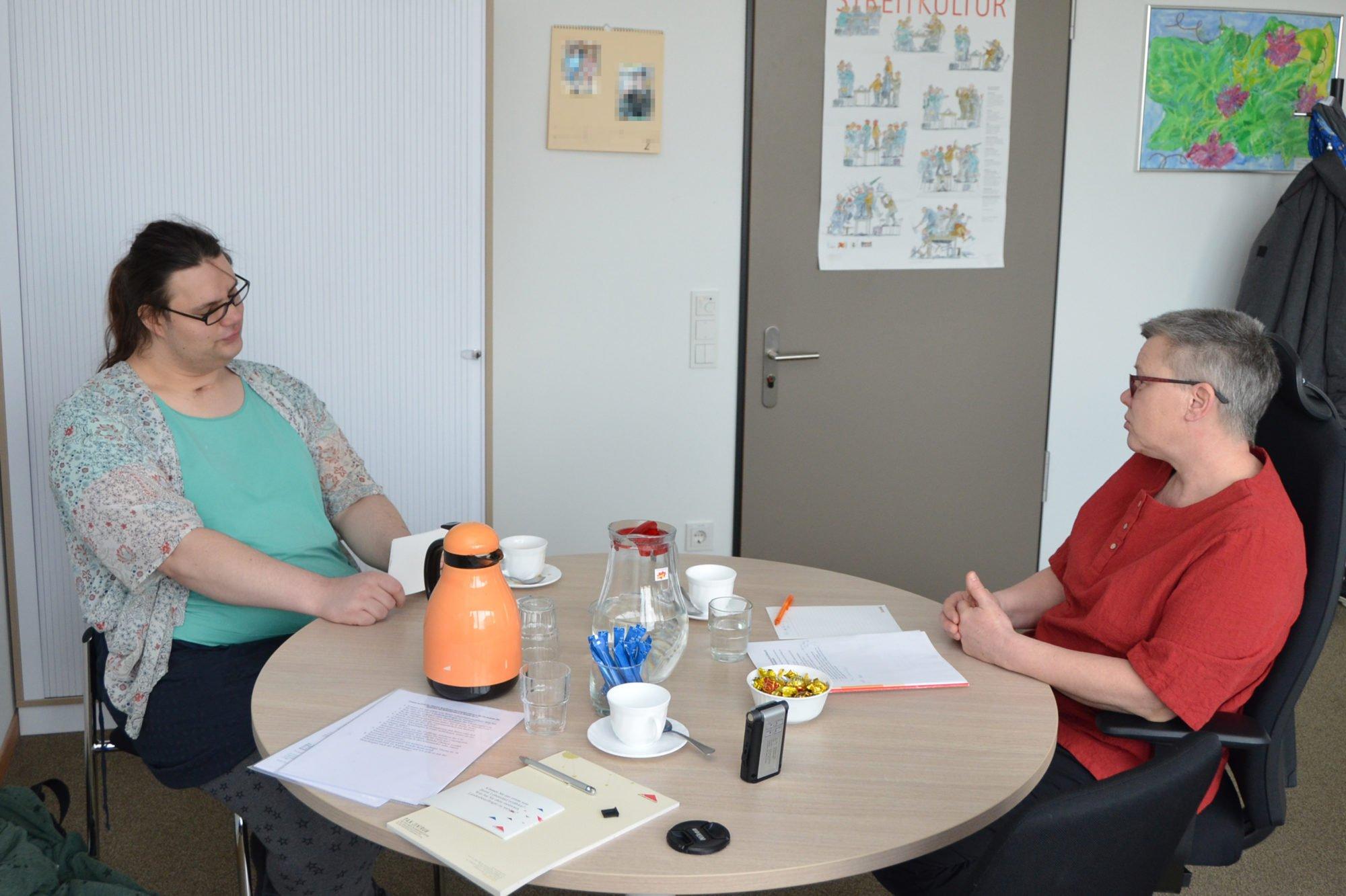 Maria Martius und Elke Mandel sitzen sich an einem runden Tisch gegenüber und unterhalten sich. Auf dem Tisch stehen Kaffeetassen sowie Wassergläser.