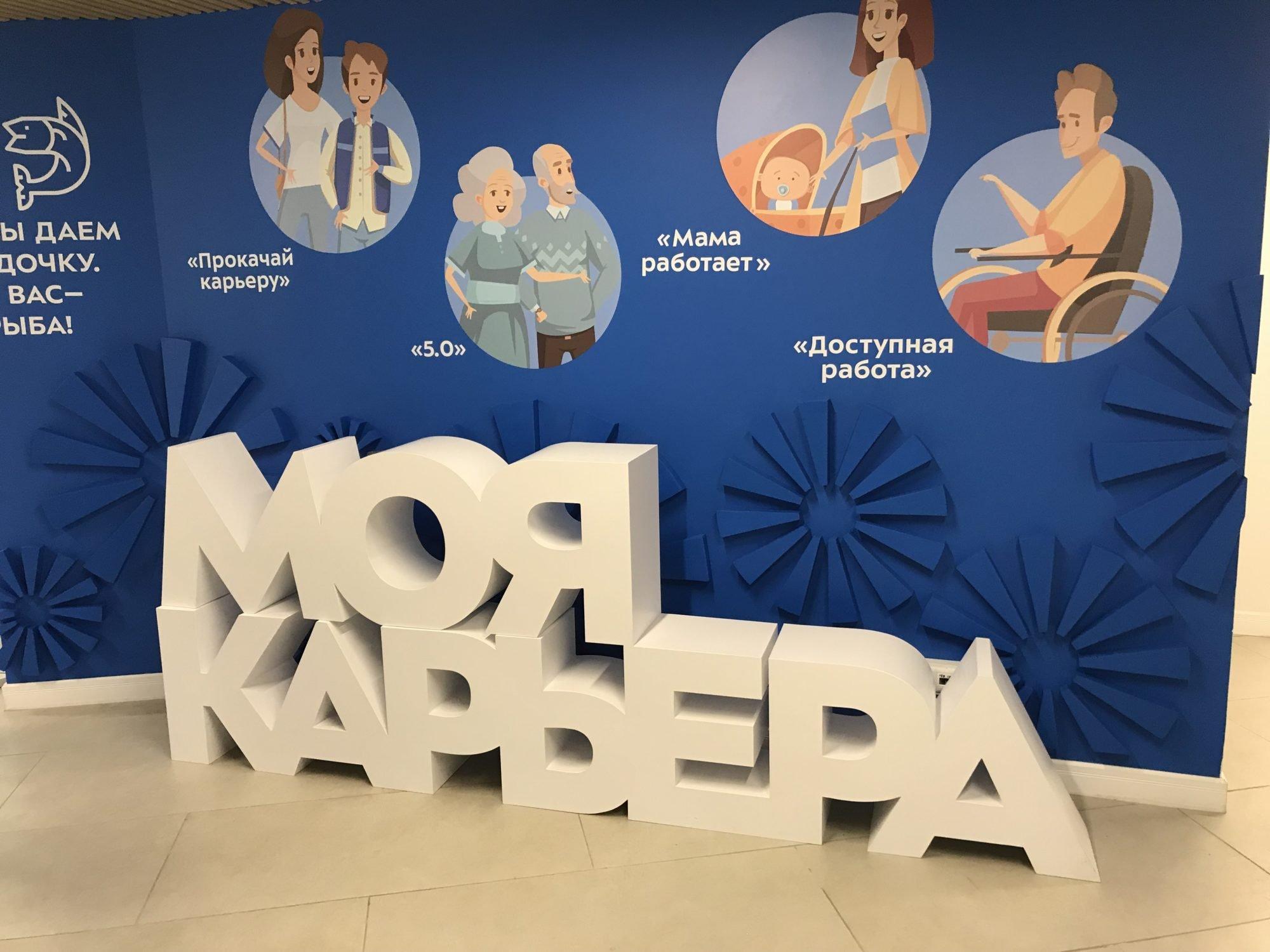 Zu sehen ist eine blaue Wand, die vier Gruppen abbildet: Menschen mit Behinderung, ältere Menschen, eine Mutter mit einem Säugling und eine Mutter mit einem Kind