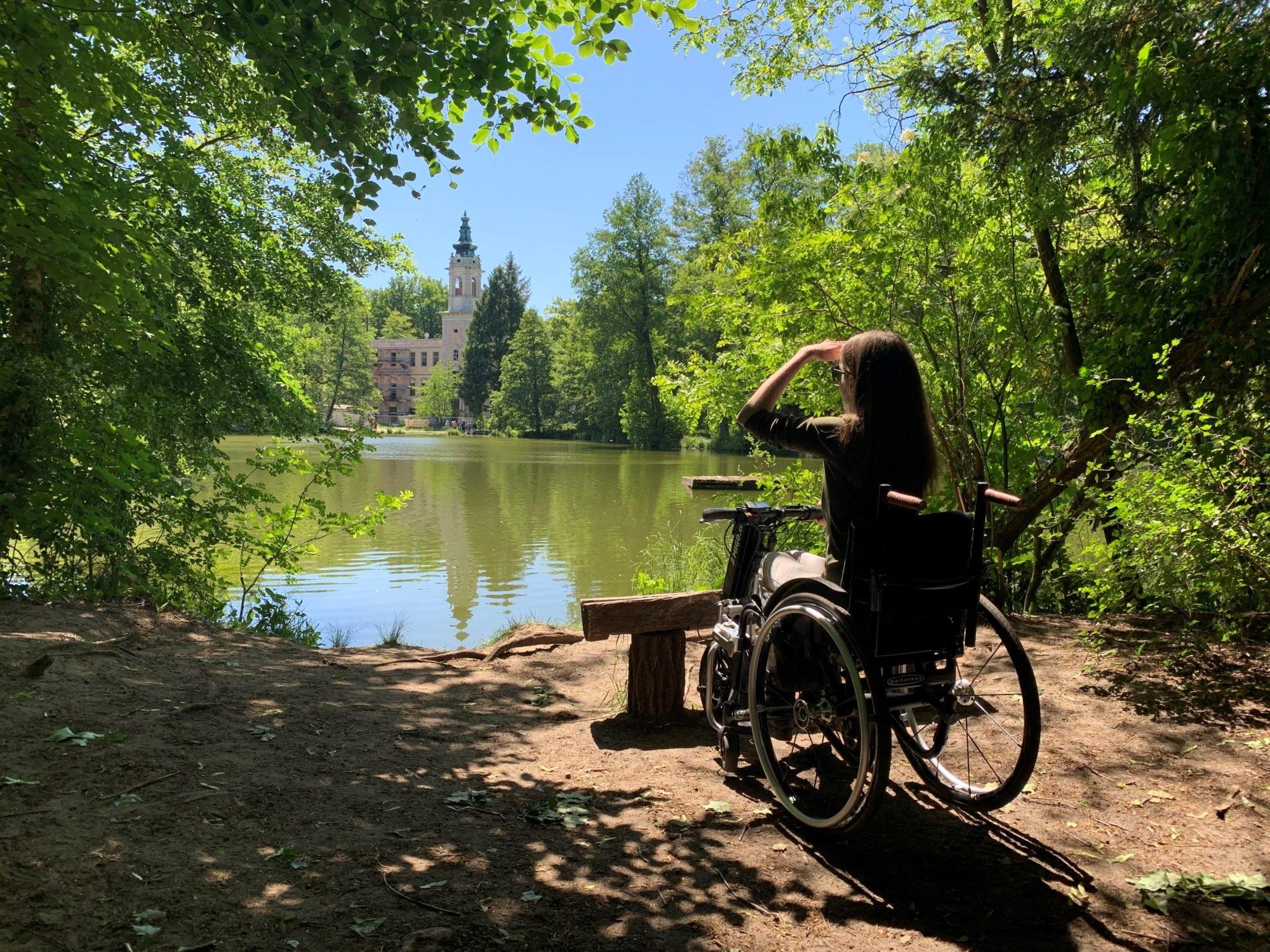 Adina sitzt mit ihrem Rollstuhl inklusive Zuggerät vor einen See im Wald und blickt in die Ferne.