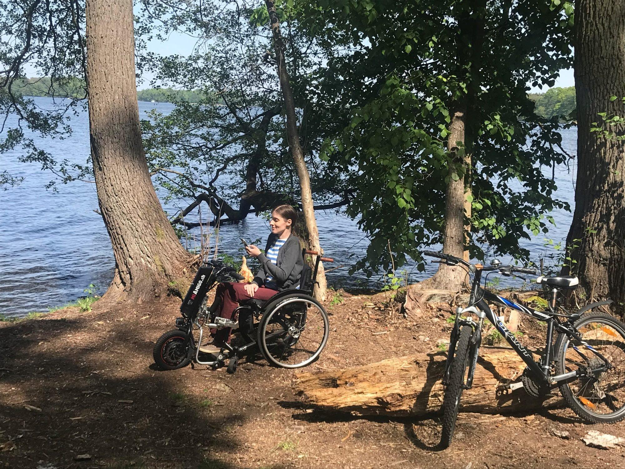 Adina sitzt mit ihrem Rollstuhl an einem See und gönnt sich eine kleine Pause von der Fahrradtour. Neben ihr steht ein Fahrrad.