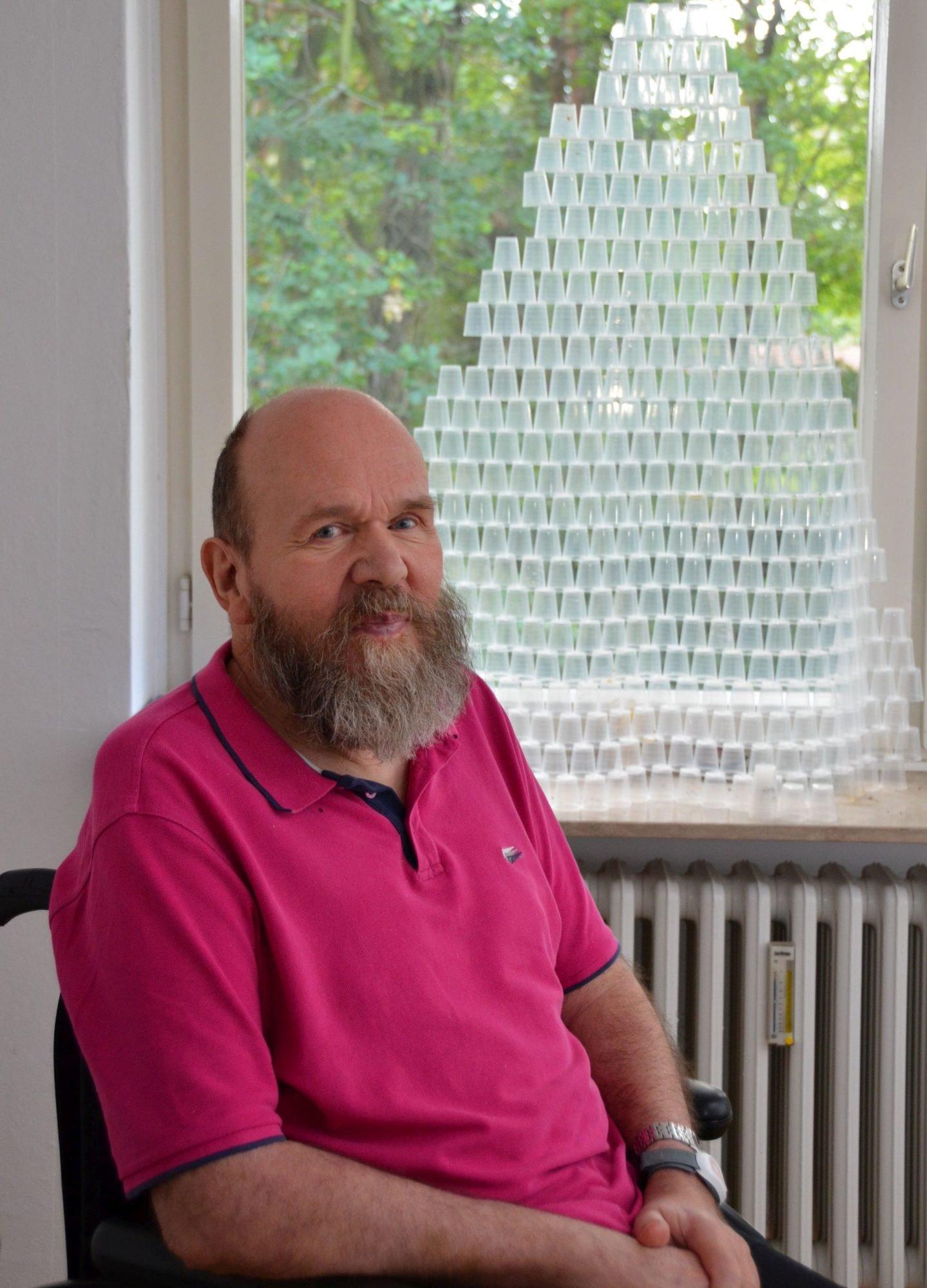 Peter Brandt vor seiner Skulptur eines DNA-Strangs aus Medikamentenbechern.