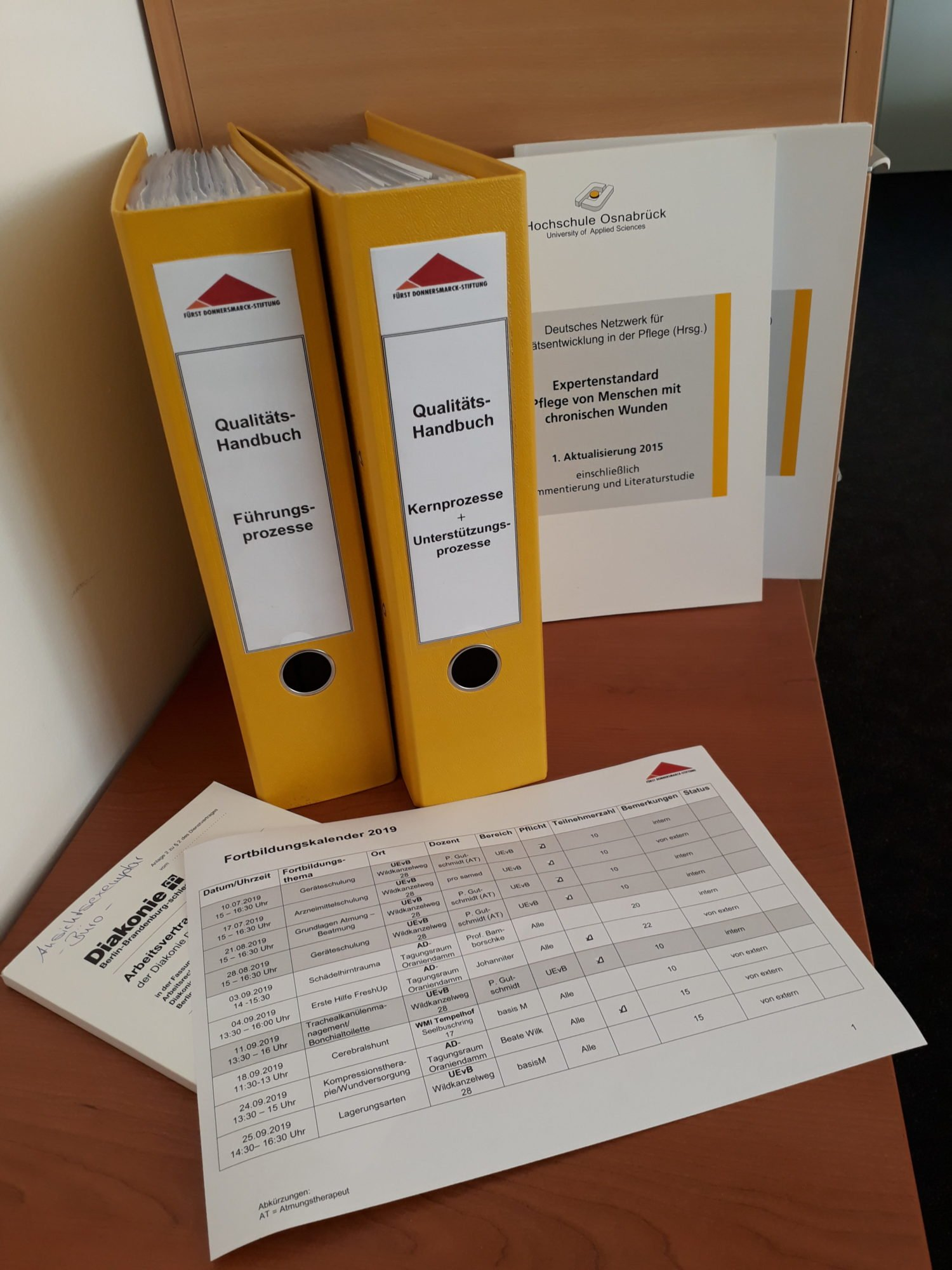 Ein Ordner, gedruckte Expertenstandards und eine Exceltabelle sind zu sehen