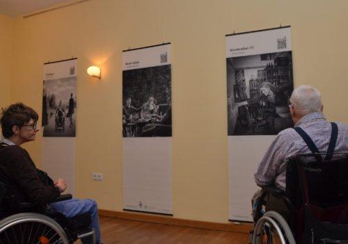 Eine Frau, links, und ein Mann, rechts, im Rollstuhl betrachten Bilder der Ausstellung.