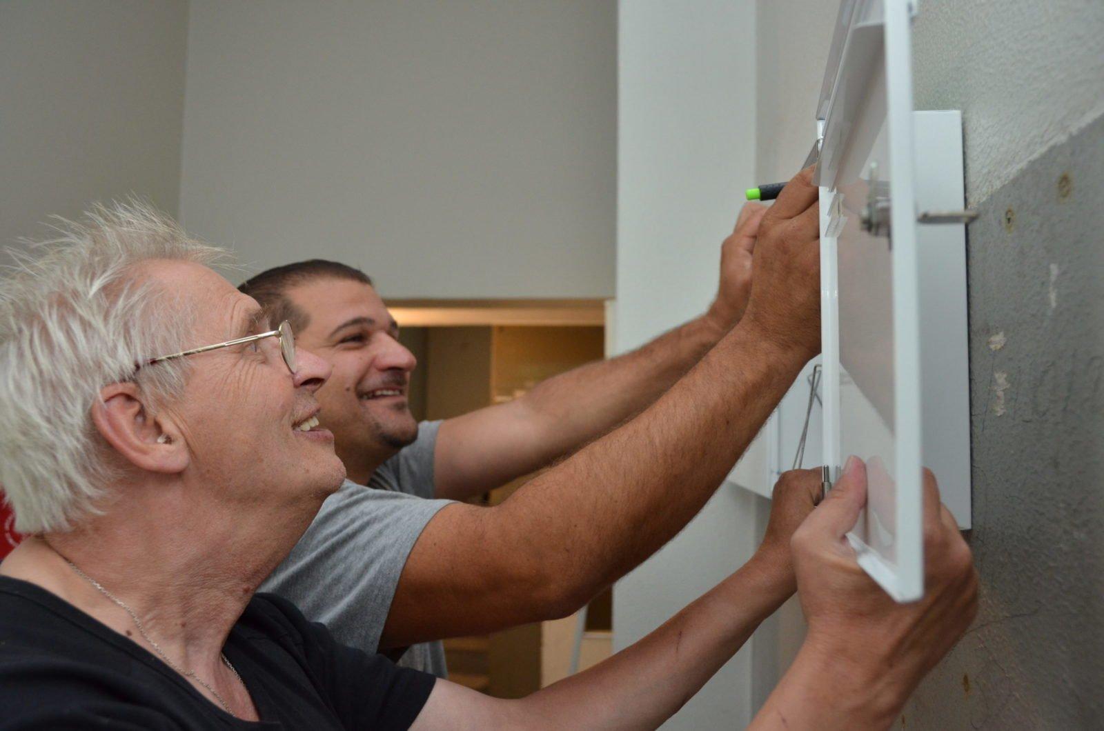 Zwei Männer bringen einen Briefkasten an der Wand an.
