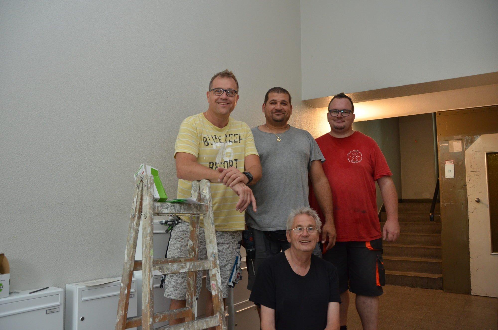 Vier Mitarbeiter des Reparaturmobils stehen in einem Hausflur und lächeln in die Kamera