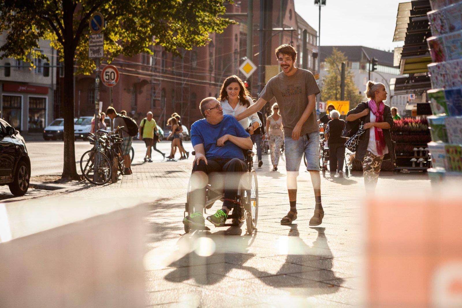 Zwei Männer und eine Frau auf Kiez-Erkundungstour. Im Hintergrund viele Geschäfte und Menschen. Ein Mann sitzt im Rollstuhl, die Frau schiebt ihn und der andere Mann läuft neben ihnen her. SIe scheinen sich zu unterhalten und lachen.
