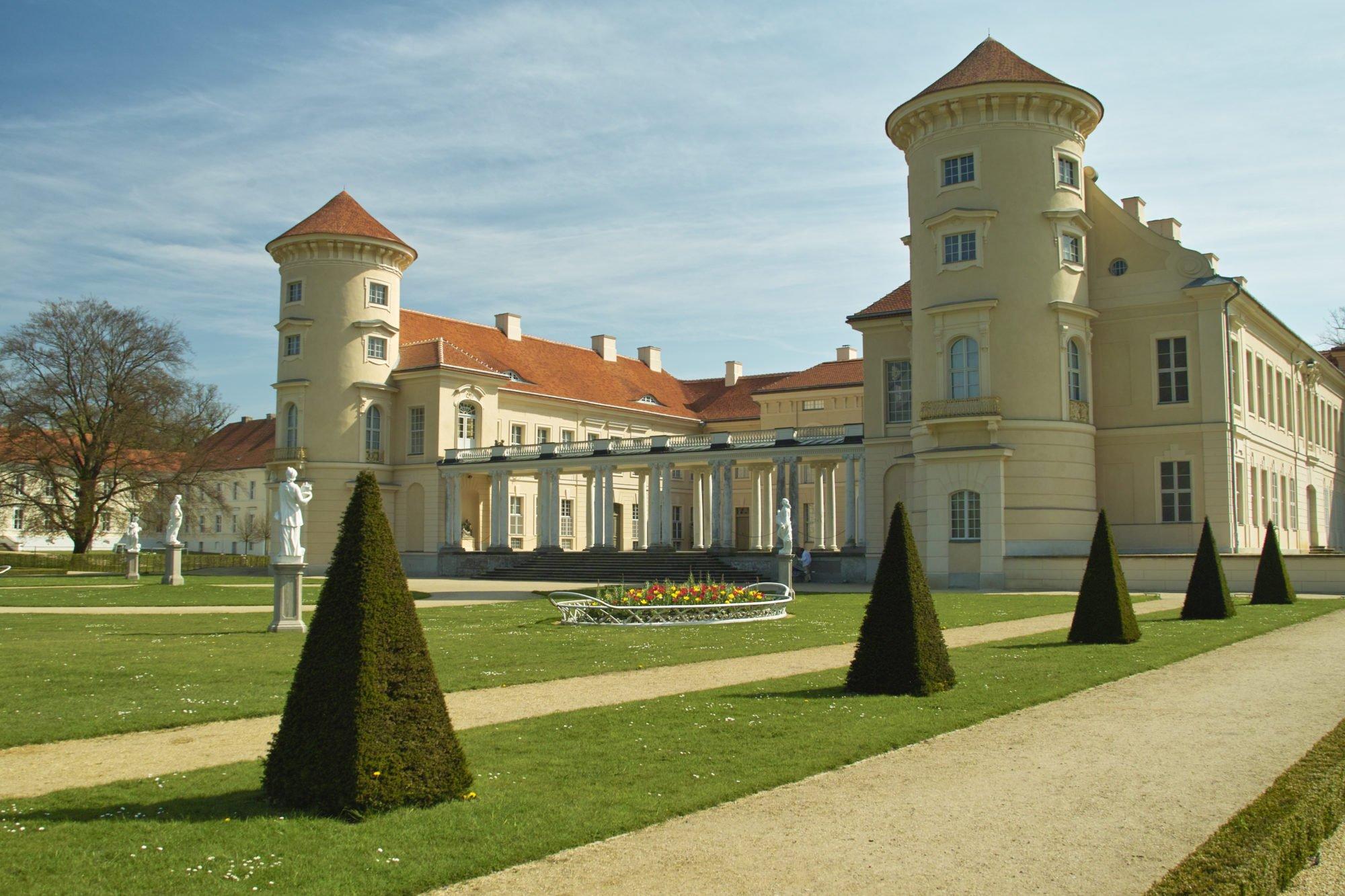 Zu sehen ist das Schloss Rheinsberg von hinten. Besonders deutlich sind die beiden Türme mit einem roten Dach und einem sandfarbenen Anstrich.