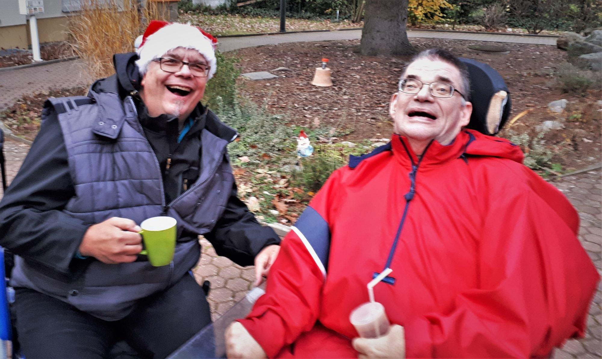 Zwei gut gelaunte Männer. Beide sitzen im Rollstuhl.