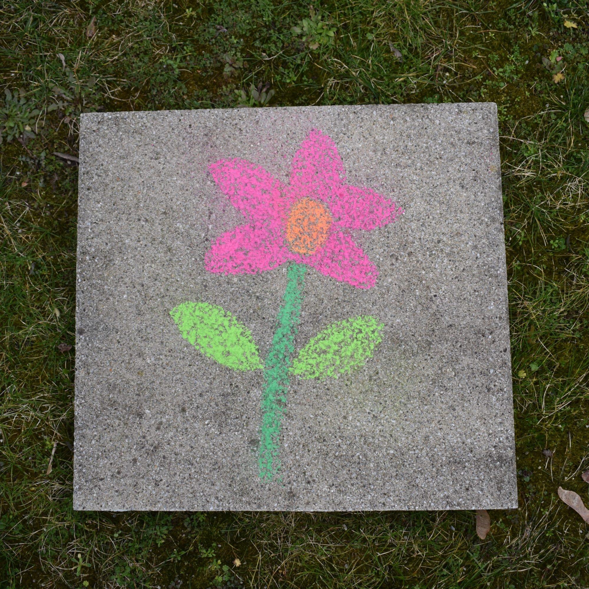 Eine Kreidezeichnung einer bunten Blume mit rosa Blütenauf einer Steinfliese.