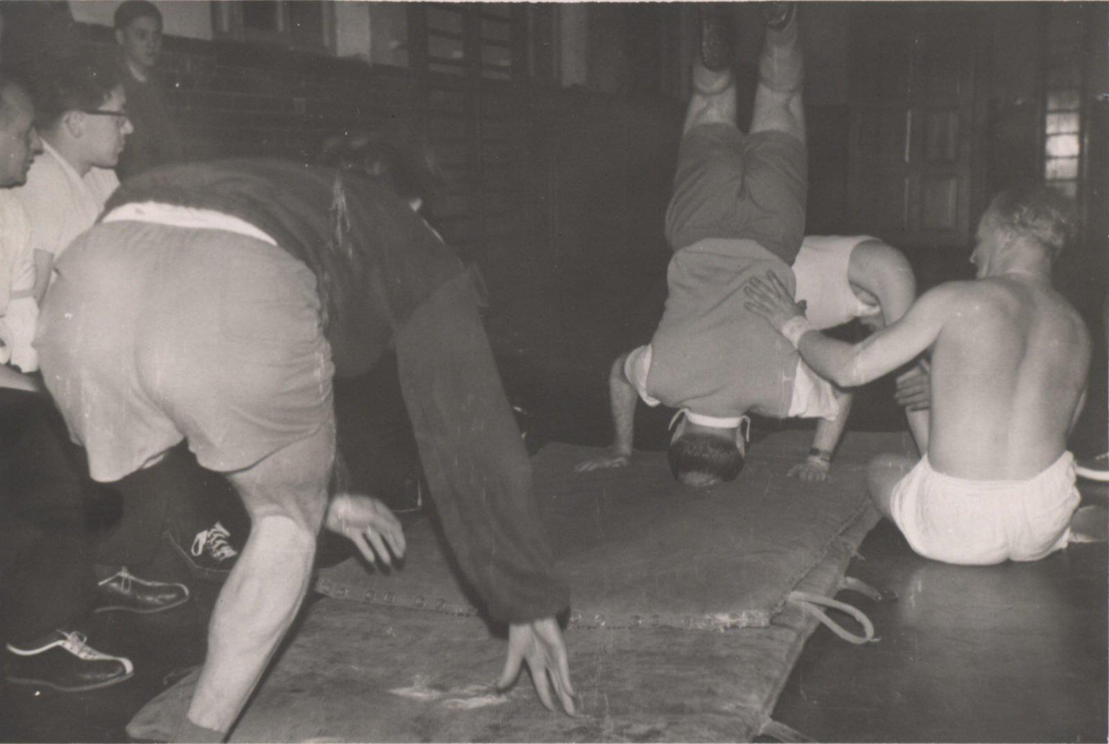 Ein altes Schwarz-Weiß-Bild aus den 60er Jahren. Es zeigt mehrere Männer, die auf Bodenmatten turnen.
