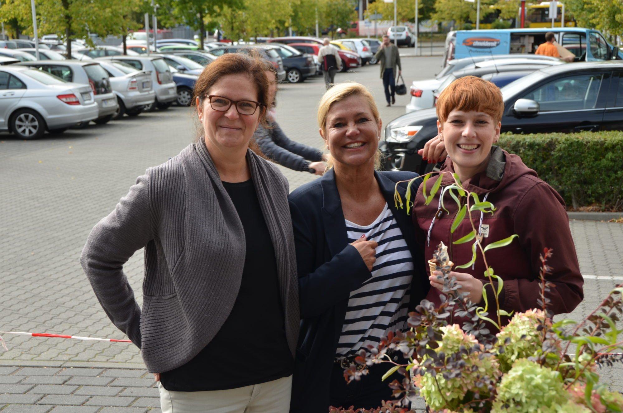 Drei Frauen nehmen sich gegegenseitig in den Arm und lächeln Richtung Kamera. IM Hintergrund ein belebter Parkplatz eines Einkaufscenters.