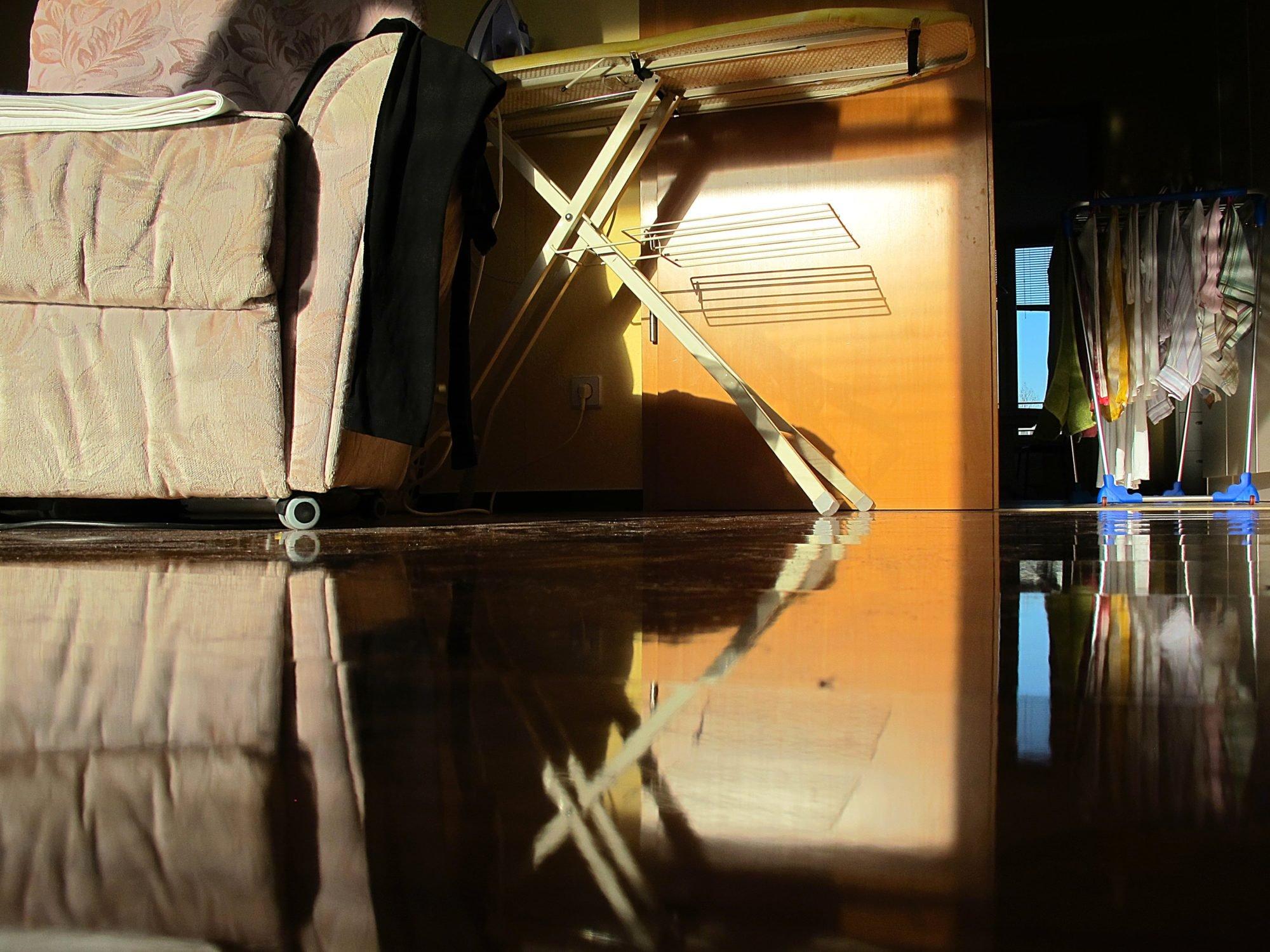 Farbfotografie: ein schummeriges Wohnzimmer mit Sessel und Bügelbrett, das sich im polierten Fußboden spiegelt