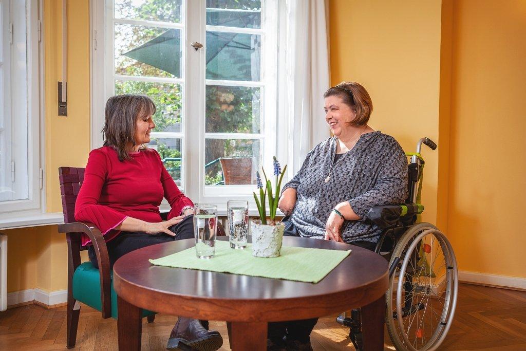 Beratungssituation: Eine lachende Frau im Rollstuhl sitzt auf der rechten Seite hinter einem dunklen, runden Holztisch einer lächelnden Frau in einem Cocktailsessel gegenüber, beide schauen sich in die Augen; im Hintergrund sieht man Garten und einen großenn, aufgespannten Sonnenschirm durch ein Altbaufenster.