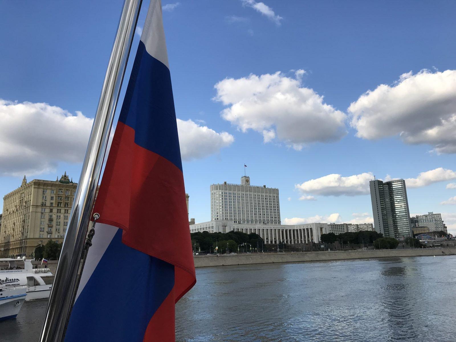 Zu sehen ist das Weiße Haus in Moskau, links im Bildvordergrund sieht man die russische Flagge