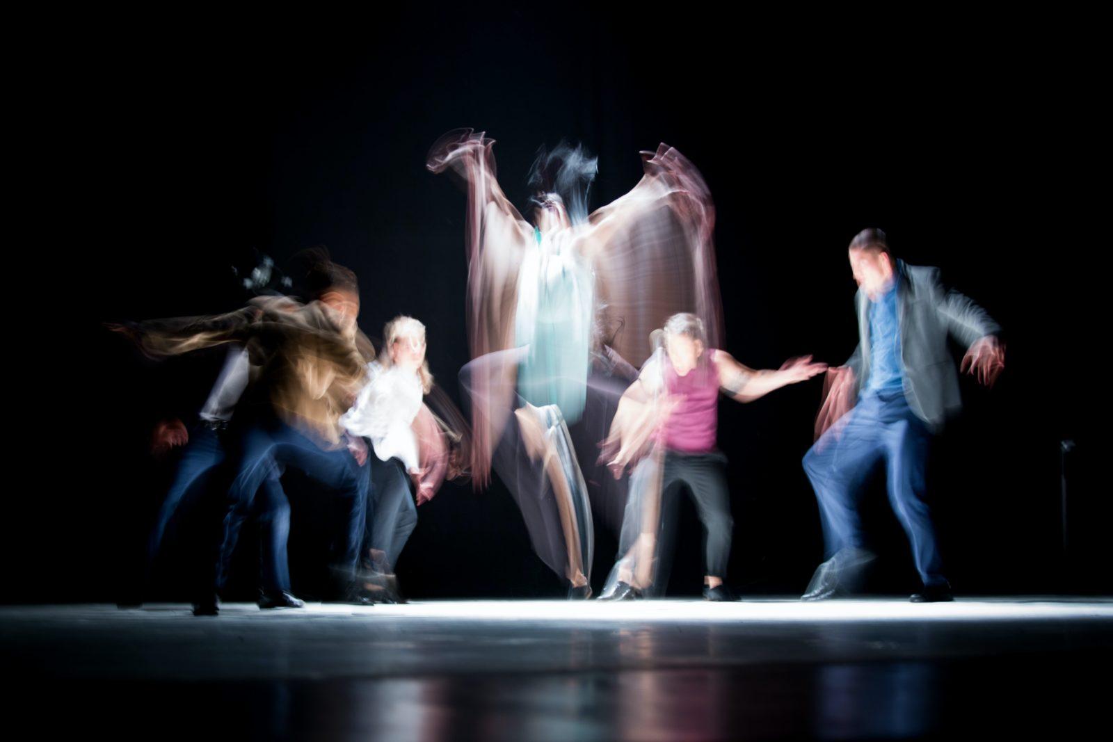 Bunte, verschwommene und schemenhafte Menschen beim Tanz vor schwarzem Hintergrund.