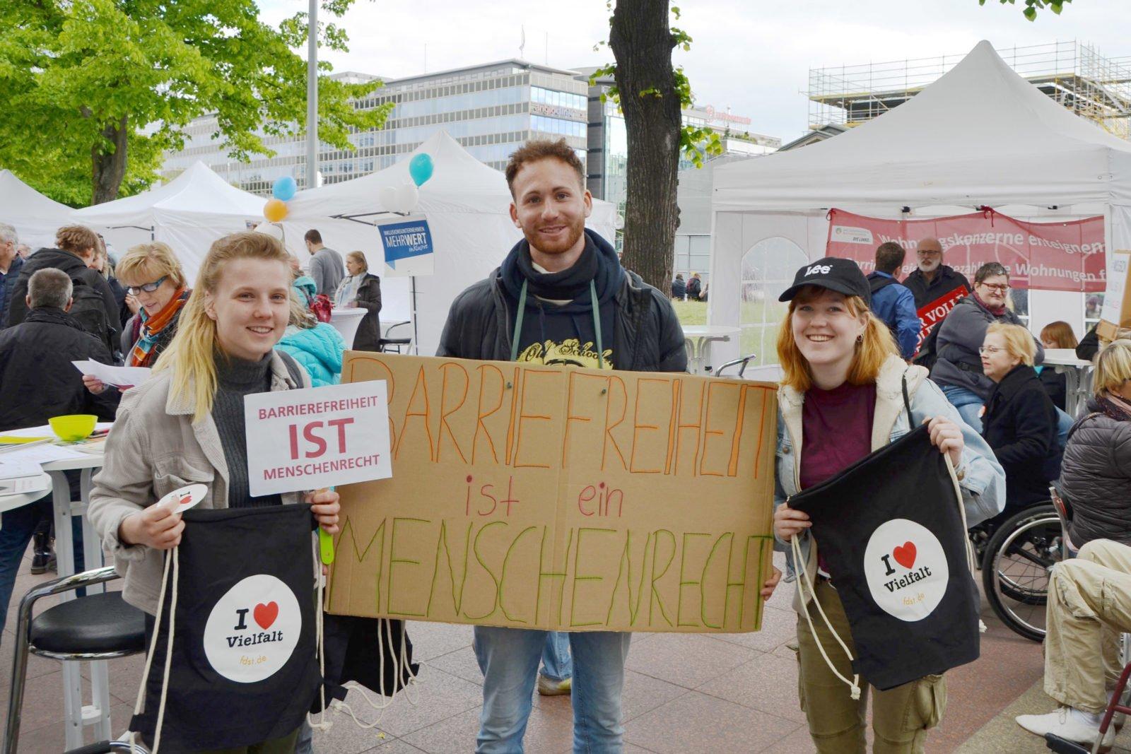 """Drei junge Menschen auf dem Protesttag, in der Mitte ein junger Mann mit einem Schild auf dem """"Barrierefreiheit ist ein Menschenrecht"""" steht, links und rechts neben ihm jeweils eine junge Dame, beide halten Beutel mit der Aufschrift I llove Vielfalt nach oben, die linke Frau außerdem ein kleineres Schild mit der Aufschrift """"Barrierefreiheit ist Menschenrecht"""""""