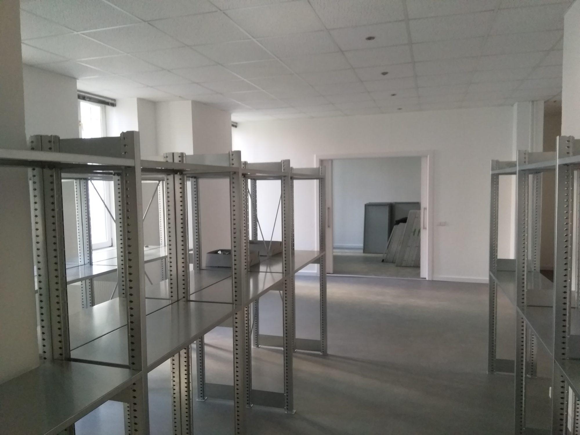 Leere Metallregale und weiße Wände - die neuen Archivräumlichkeiten.