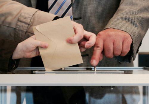 Hände werfen Wahlunterlagen in eine Urne.