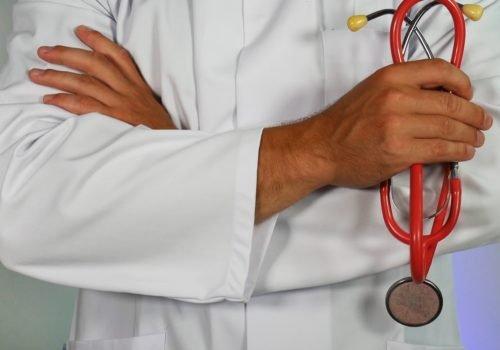 Symbolfoto: Nahaufnahme eines Arztes in seinem Kittel. Man sieht nur die Arme, die er über seinem Kittel verschränkt. In der linken Hand hält er ein Stethoskop.