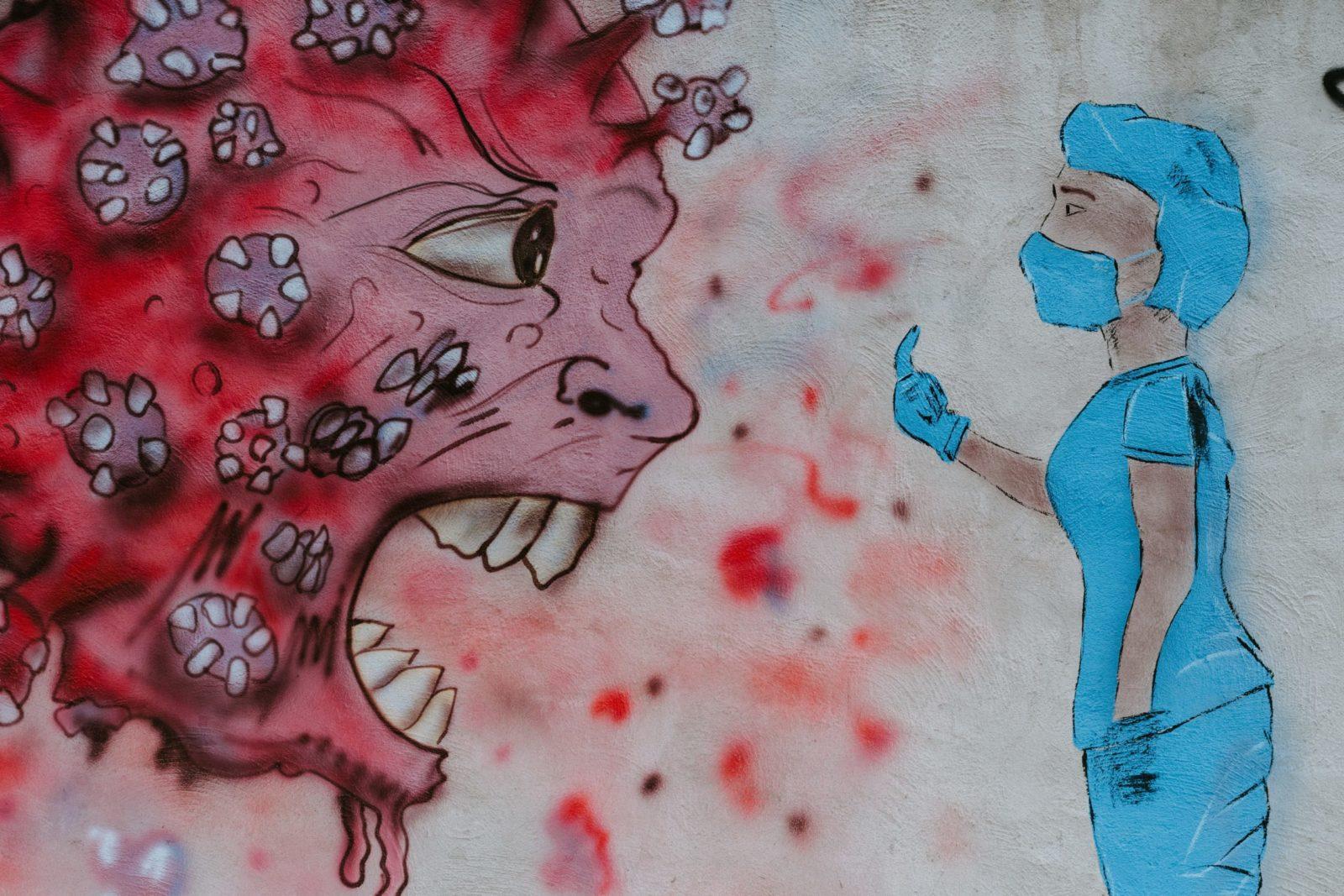 Graffiti auf Hauswand: Eine in Schutzkleidung gekleidete Person zeigt einem Cartoon-Coronavirus (mit großen Augen und scharfen Zähnen) den Mittelfinger.