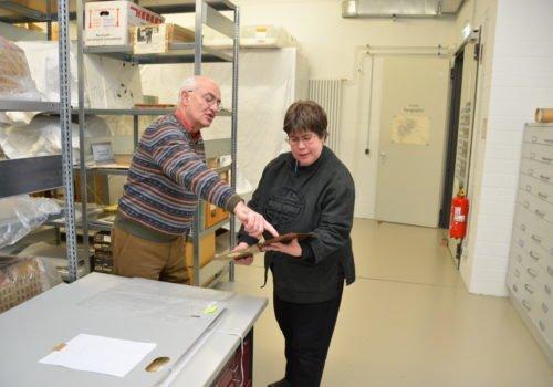 Gerd Heinemann steht links und Anke Köhler rechts im großen Depot-Raum. IM Hintergrund sind große Regale und Fächer mit Exponaten zu erkennen. Heinemann zeigt Köhler ein Exponat und deutet mit dem Finger an eine bestimmte Stelle.