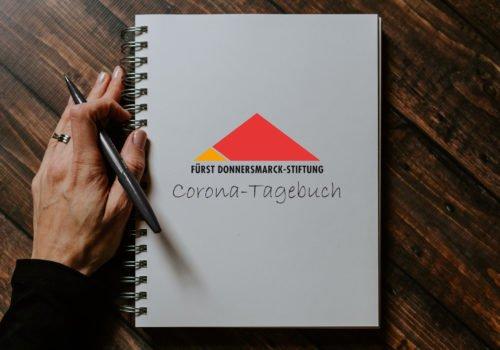 Ein Ringbuch mit FDST-Logo und der Aufschrift Corona-Tagebuch. Daneben liegt eine Hand, die einen Stift in der Hand hält.